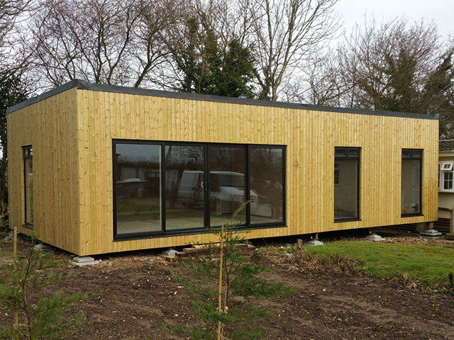timber clad self build home with glazed doors and windows
