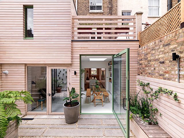 timber clad extension with green glazed door - grand designs