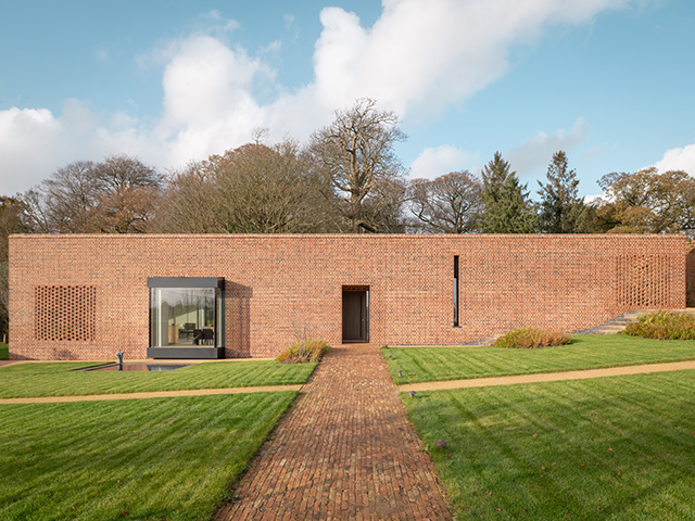Exterior of a simple single storey house built in red brick that stands out against the green landscape
