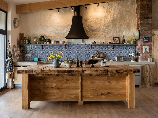 An island made from railway sleepers stands in front of a run of timber cabinets with concrete worksurface