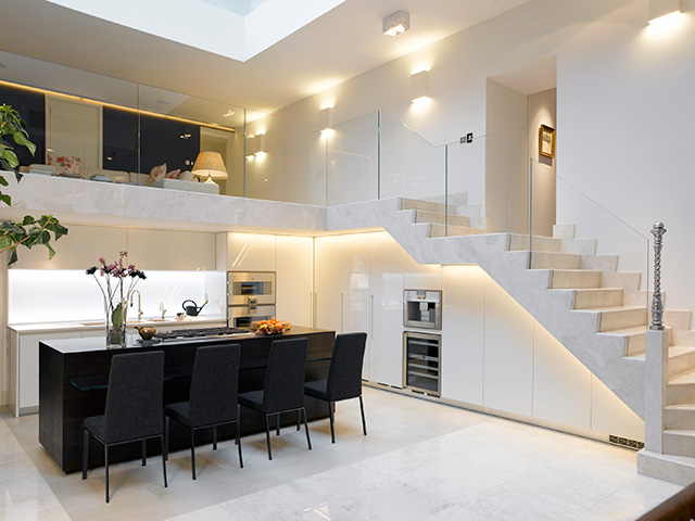 White marble kitchen with black island unit in the centre. Another Grand Designs most expensive home.