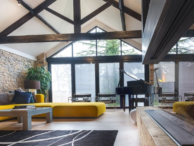 interior of converted barn with piano and yellow sofa