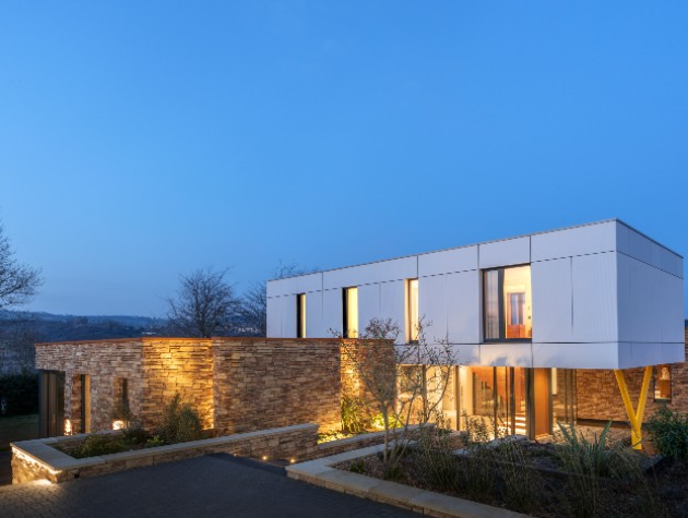 contemporary home with stone clad ground floor and white cantilevered first floor