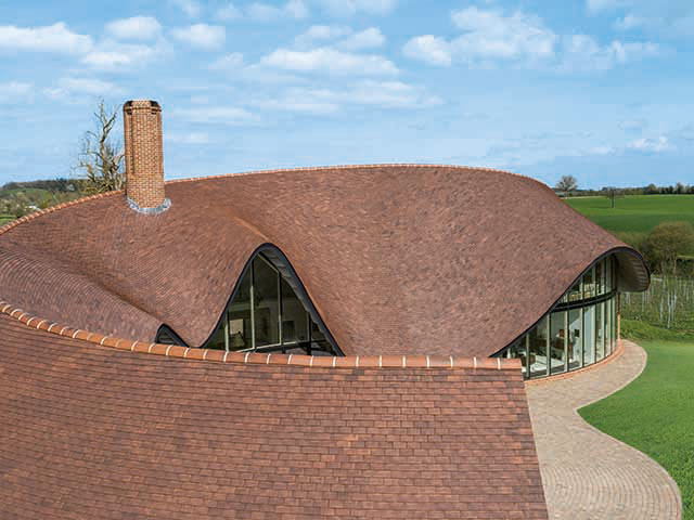 View of roof with red clay tiles as part of roofing materials guide