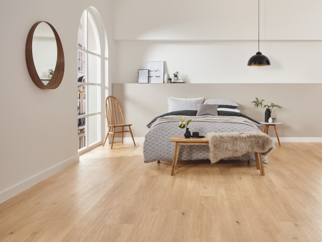bedroom with bed arched window and lvt flooring