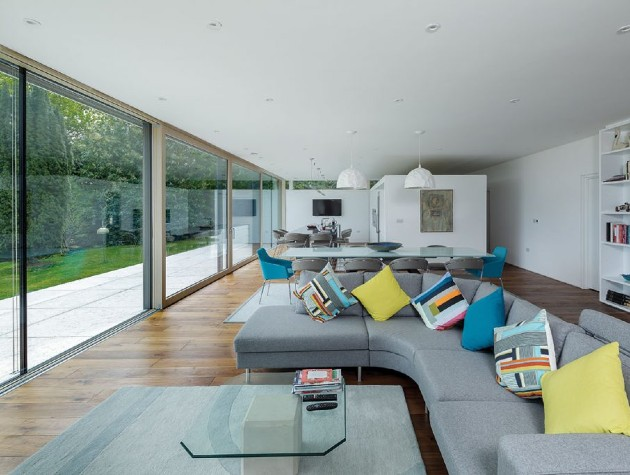 large open plan room with sofa shelves tables and sliding glass doors