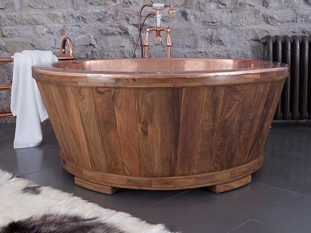 Copper and teak freestanding bath in room with grey flooring and cream rug beside