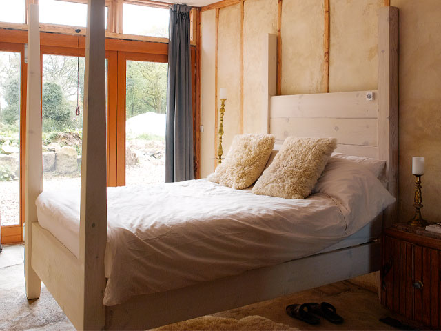 A four-poster bed in limed oak in the Grand Designs earthship house