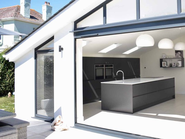 Exterior view of a kitchen extension with Masterclass Kitchens large kitchen island and bifold doors linking the kitchen and garden