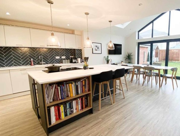 Large kitchen extension with wooden floors white Masterclass Kitchens peripheral units blue kitchen island dining table and a sofa