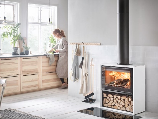 woman cleaning in kitchen wood burning stove and logs in foreground