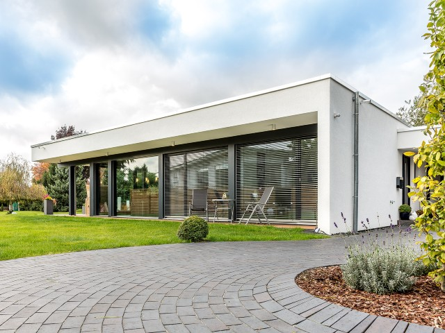 single storey Meisterstueck Haus with wrap-around windows and white paint finish
