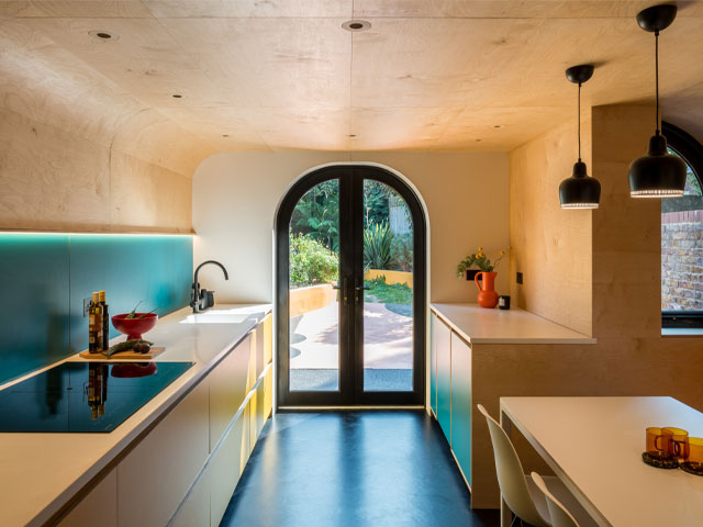 A colourful kitchen remodelled with curved plywood and budget formica units