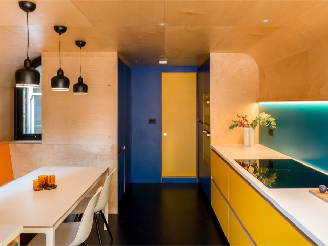 Formica kitchen units in Spectrum Yellow with Birch ply curved kitchen surfaces