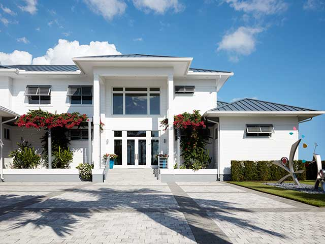 Florida villa outside with white walls, plants and dark ceilings