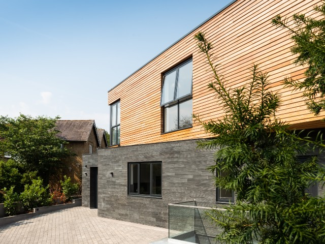 designing your eco home: timber and slate clad self-build house with large windows and lush green plants